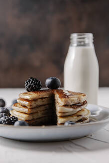 Still life of a stack of homemade pancakes with berries and syrup on a plate, and a bottle glass of milk in background. - CAVF78574