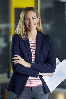 Portrait of smiling businesswoman holding papers in office - RBF07481