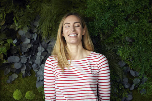 Portrait of happy woman with closed eyes in front of a green wall - RBF07484