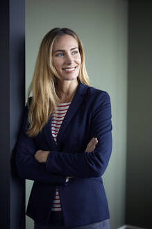 Portrait of smiling businesswoman leaning against a wall - RBF07493