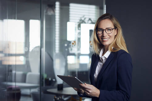 Portrait of smiling businesswoman holding tablet in office - RBF07520