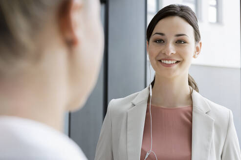 Portrait of smiling young businesswoman with earphones and colleague in office - BMOF00381