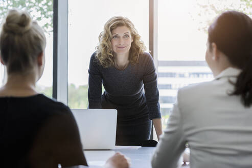 Businesswomen having a meeting in bright office - BMOF00393