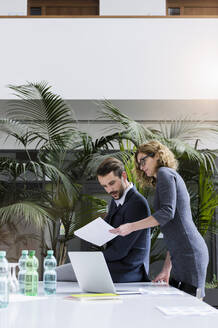 Businessman and businesswoman looking at document in office - BMOF00396