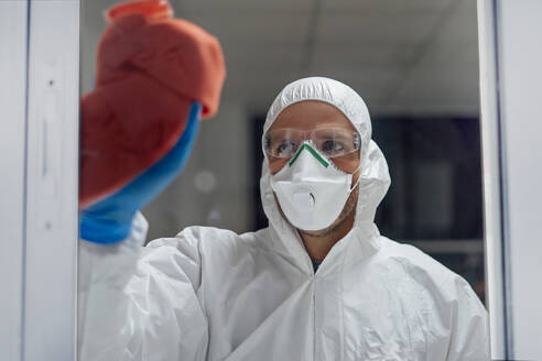 Cleaning staff desinfecting hospital against contageous virus, wearing protective clothing - CJMF00293