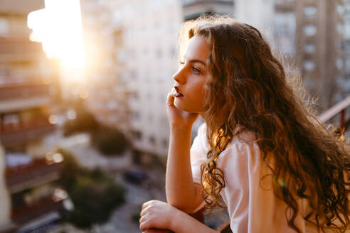 Portrait of beautiful young woman on balcony at sunset - TCEF00458