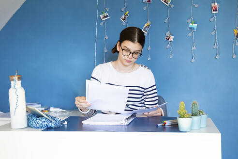 Portrait of girl sitting at desk at home doing homework - LVF08762