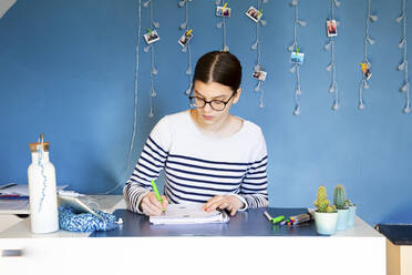 Portrait of girl sitting at desk at home doing homework - LVF08765