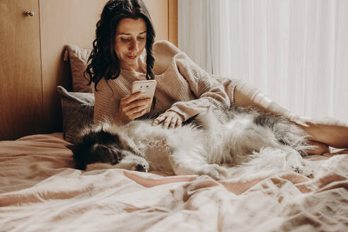 Portrait of woman relaxing with her dog on bed looking at smartphone - GMLF00002