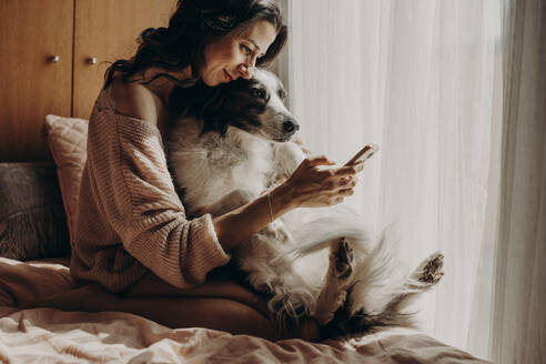 Smiling woman sitting on bed with her dog taking selfie with smartphone - GMLF00005