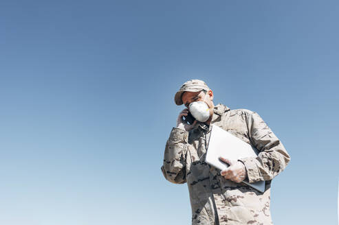 Soldier with face mask on emergency operation, using smartphone, carrying laptop - JCMF00565