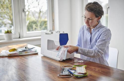 Woman sewing face masks at home - DIKF00416