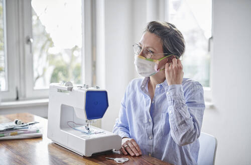 Woman trying face mask, she is sewing at home - DIKF00419