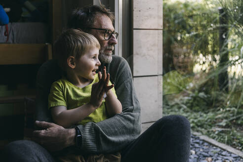 Father and little son sitting together on the floor at home looking out of window - MFF05407