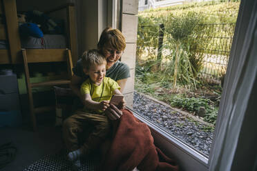 Mother and little son sitting on the floor at home using smartphone - MFF05410