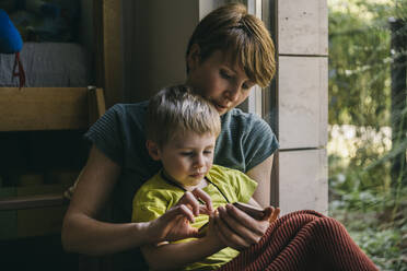 Mother and little son cuddling at home looking at smartphone - MFF05413