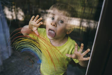 Portrait of little boy standing behind balcony door licking glass pane with drawn rainbow - MFF05419