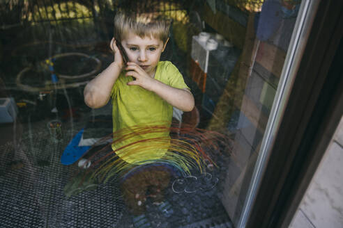 Portrait of little boy on the phone standing behind balcony door - MFF05422