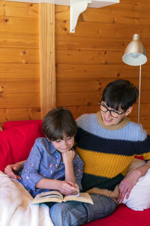 Mother and daughter reading a book on couch in a wooden cabin - VSMF00035