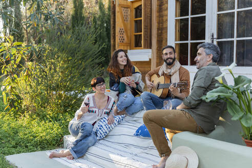 Friends playing music on the guitar and drinking wine outside a cabin in the countryside - VSMF00053