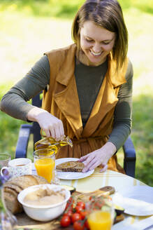 Woman pouring olive oil on bread - VSMF00101