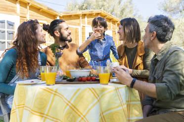 Fanilyand friends enjoying a healthy vegan breakfast in the countryside - VSMF00104