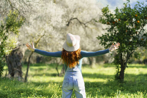 Redheaded woman wearing a hat enjoying the countryside with open arms - VSMF00140