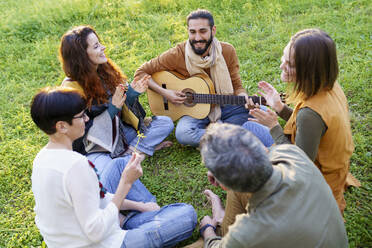 Group of friends playing music with the guitar sitting on the grass in the field - VSMF00164