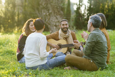 Group of friends playing music with the guitar sitting on the grass in the field - VSMF00167