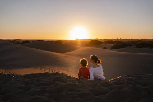 Mother and daughter sitting in sand dunes at sunset, Gran Canaria, Spain - DIGF09543