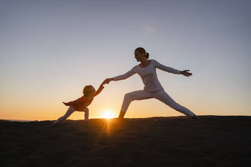 Mother and daughter practicing yoga in sand dunes at sunset, Gran Canaria, Spain - DIGF09549