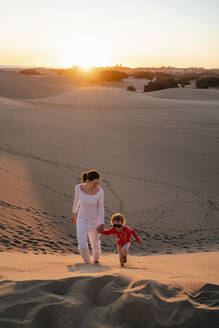 Mother and daughter walking up sand dune at sunset, Gran Canaria, Spain - DIGF09552