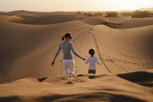 Mother and daughter walking hand in hand in sand dunes, Gran Canaria, Spain - DIGF09585