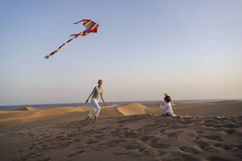 Mother and daughter flying kite in sand dunes, Gran Canaria, Spain - DIGF09594