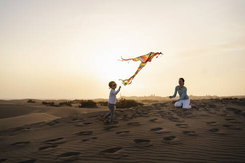Mother and daughter flying kite in sand dunes at sunset, Gran Canaria, Spain - DIGF09597