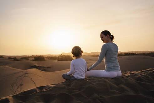 Mother and daughter practicing yoga in sand dunes at sunset, Gran Canaria, Spain - DIGF09600