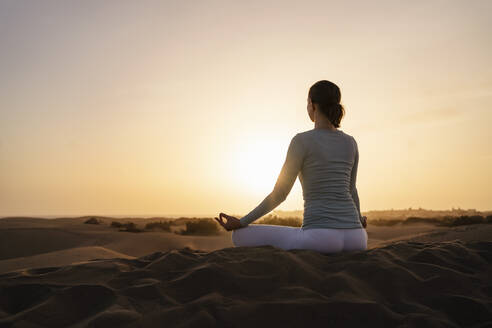 Woman practicing yoga in sand dunes at sunset, Gran Canaria, Spain - DIGF09603