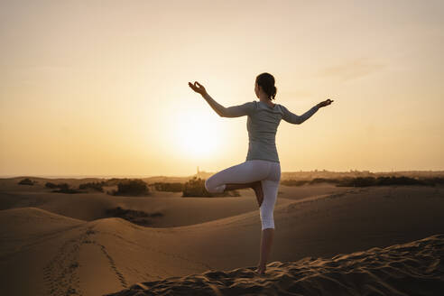 Woman practicing yoga in sand dunes at sunset, Gran Canaria, Spain - DIGF09612