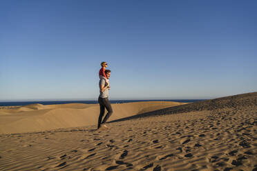 Father carrying daughter on shouldres in sand dunes, Gran Canaria, Spain - DIGF09618
