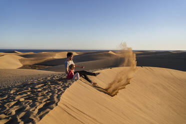 Father and daughter sitting on sand dune, Gran Canaria, Spain - DIGF09624