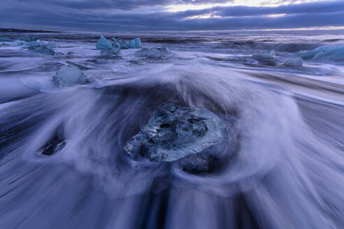 Iceland, Ice chunks lying at shore of Jokulsarlon at dusk - TOVF00166