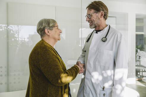 Doctor and senior patient in medical practice shaking hands - MFF05423