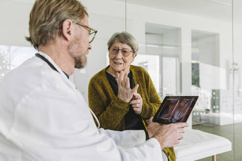 Doctor discussing x-ray image of broken hand with senior patient - MFF05438