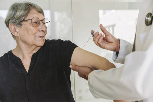 Doctor injecting vaccine into senior patient's arm - MFF05450