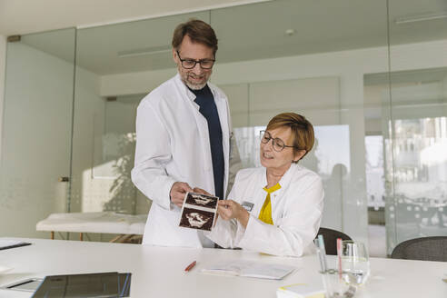 Two doctors discussing ultrasound images of fetus - MFF05477