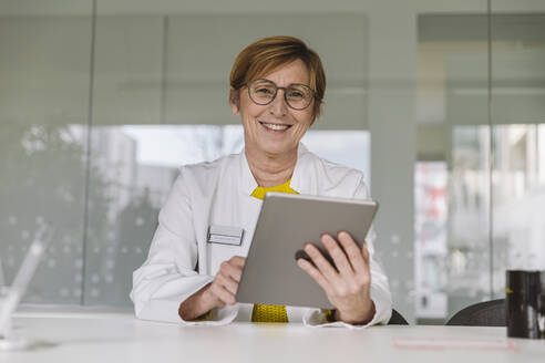 Portrait of smiling doctor sitting at desk using tablet - MFF05498