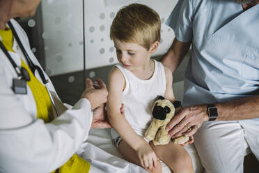 Pediatrist injecting vaccine into arm of toddler - MFF05525