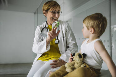 Peditrician with finger dolls and toddler in medical practice - MFF05531