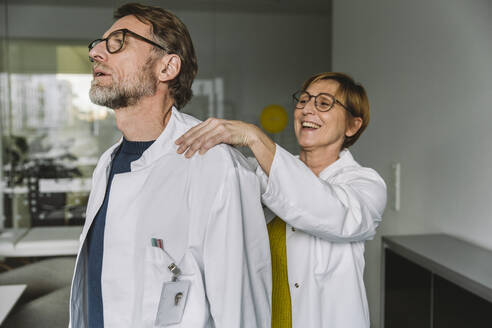 Doctor massaging shoulder of a colleague - MFF05537