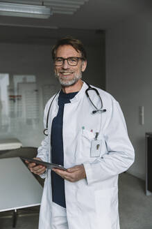 Portrait of smiling doctor holding tablet - MFF05549